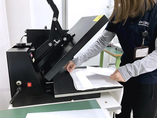 昇華転写プリントで専用用紙に印刷したオリジナルデザインはプリントしたTシャツやタオル、バッグに乗せてプレス機で熱して昇華インクを染めます。