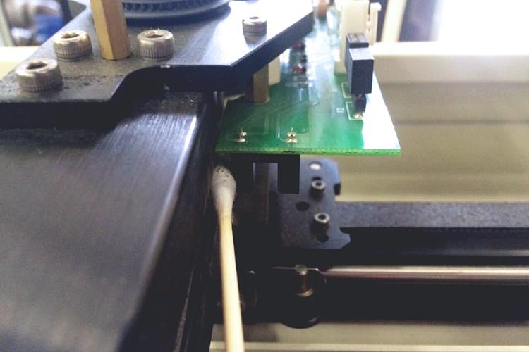レーザーカッター・レーザー加工機のヘッド部センサーの清掃方法:アルコールで湿らせた綿棒でホコリが溜まっているセンサー外側も清掃します。