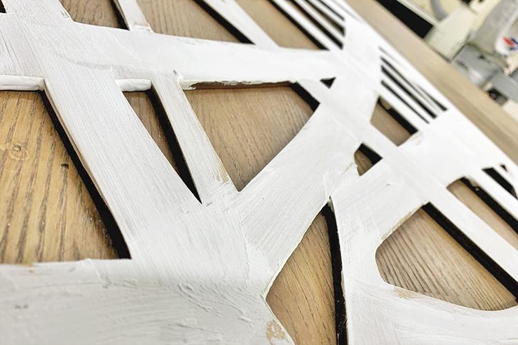 MDF製壁面パネルに、刷毛で質感が水に溶かした紙粘土に近い下地材を塗る