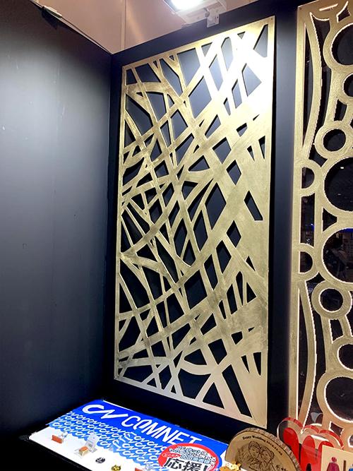レーザーカット後に下地材とゴールドの塗装を施したMDF製壁面パネル(「SIGN EXPO 2019」コムネット展示ブースに出展)
