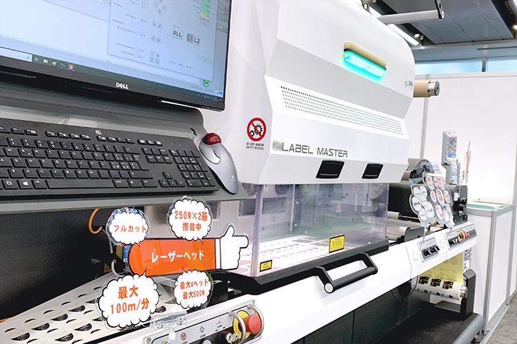 ラベルフォームジャパン2019でコムネット株式会社が出展した、シール・ラベル向けロール対応のレーザー加工機(レーザーカッター) SEIシリーズ LabelMaster(ラベルマスター)のレーザーヘッドの紹介