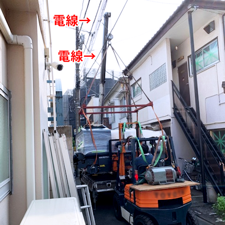 株式会社エトワール様のレーザー加工機の搬入・設置③:搬入口までたどり着き、機械をユニックで降ろすのですが、絶妙な高さに電線が!